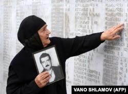 Грузинська жінка із фотографію свого родича біля пам'ятника жертвам грузинсько-абхазької війни 1992–1993 років. Тбілісі, 27 вересня 2009 року