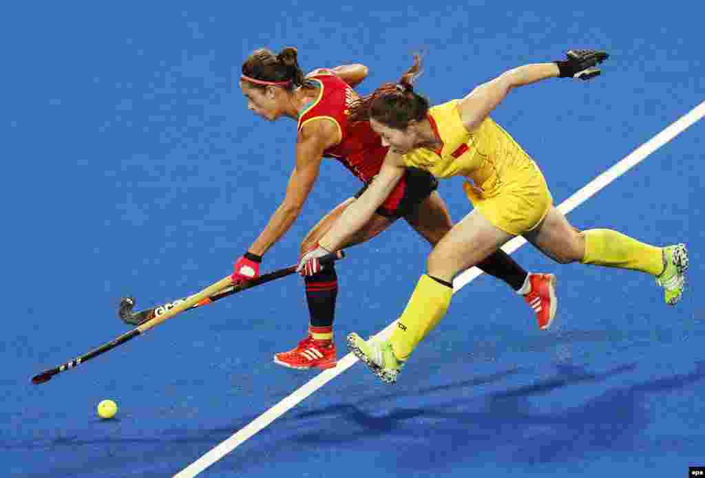 Rocio Ybarra (left) of Spain in action against Peng Yang of China during their women's field hockey preliminary-round match.