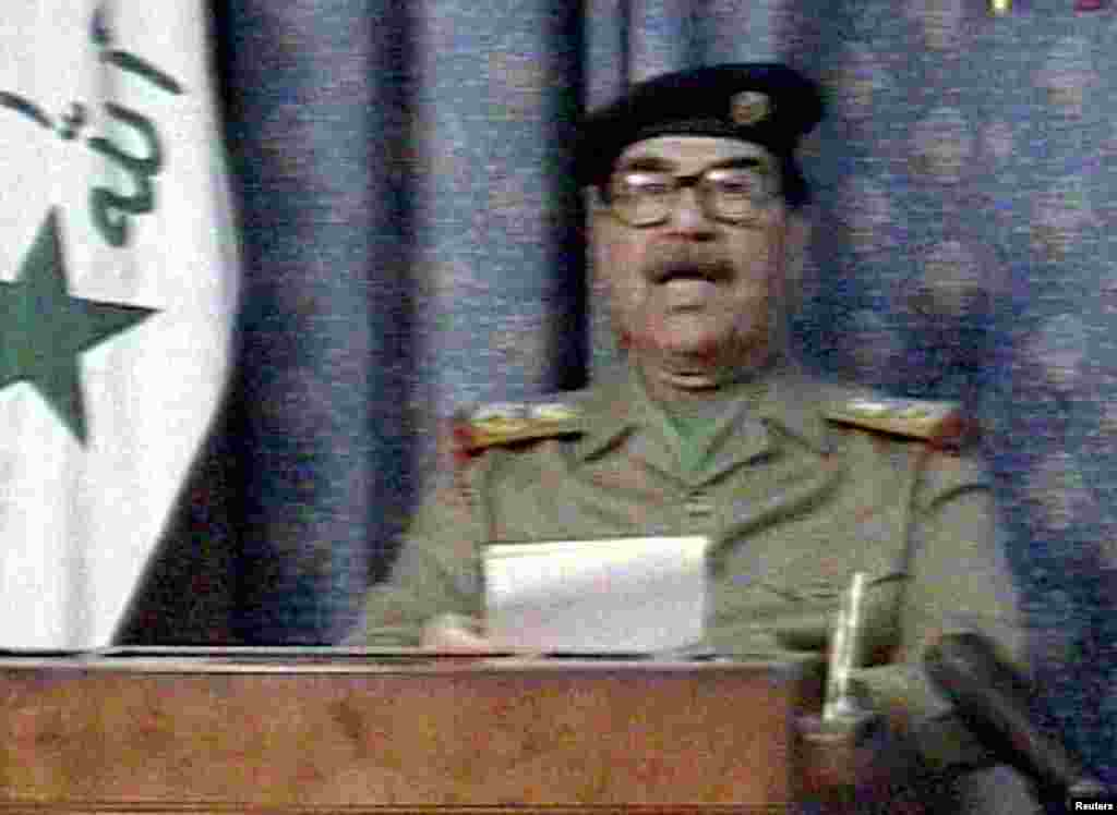 "Iraqi President Saddam Hussein appears on state television just hours after the United States launched its invasion to overthrow him. In his speech, Saddam said, ""The criminal little Bush has committed a crime against humanity."""