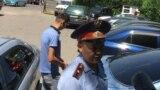 Полицейский у офиса Казахстанского бюро по правам человека, где было совершено нападение на журналистов, в том числе репортеров Азаттыка. Алматы, 22 июля 2019 года.
