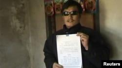 Незрячий китайский диссидент Чен Гуанченг показывает петицию, стоя у входа в свой дом в селе Линю. 27 апреля 2012 года.