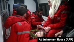 Сирийские сотрудники Международного Красного Креста эвакуируют ребенка на окраине Дамаска 26 декабря 2017 года