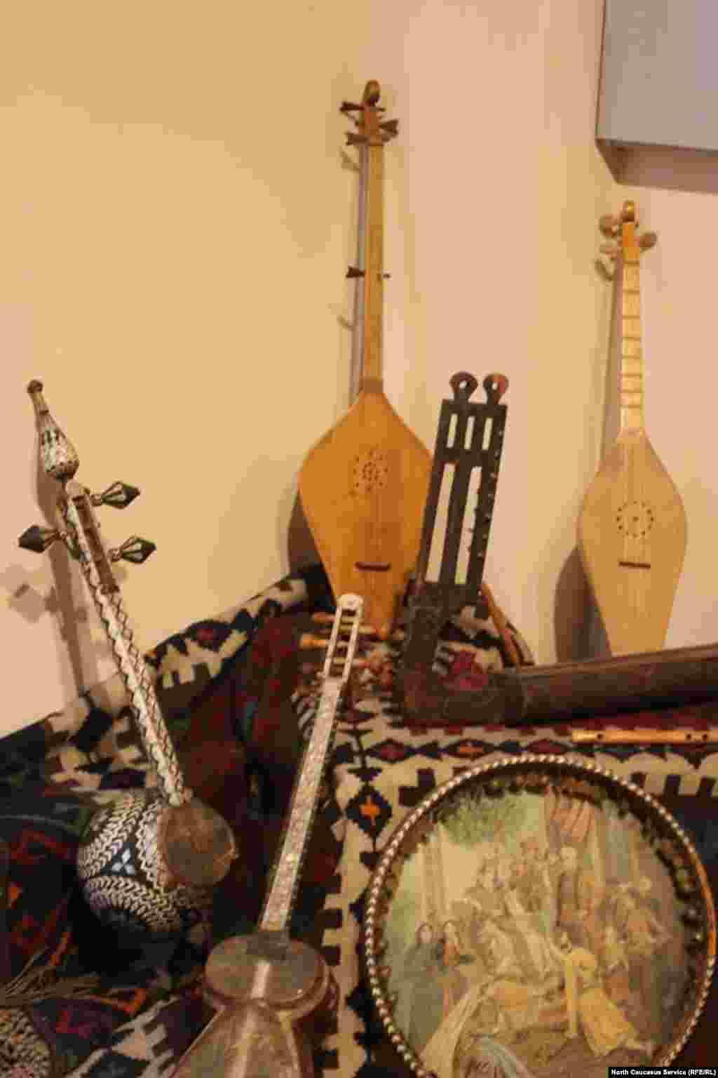 """Струнные музыкальные инструменты пандури, чонгури, кнари, дайра. На дайре изображена сцена из поэмы Ш.Руставели """"Витязь в тигровой шкуре""""."""