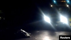 U.K. -- A video grab shows a sheet-covered body lying on a road near an ambulance in the gated private community of St George's Hill in Weybridge, 10Nov2012