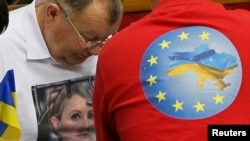 Украин Радасында оппозициячыл депутаттар сессия учурунда Юлия Тимошенкону жана Евроинтеграцияны жактаган футболкачан жүрүшөт. Киев, 8-ноябрь 2013