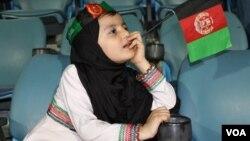 ارشیف، یوه افغانه ماشومه د دپۍ په یوه لوبغالي کې د کرکټ لوبه ننداره کوي