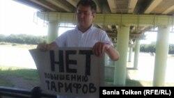 """Житель города Атырау Талгат Аян держит плакат с надписью: """"Нет повышению тарифов"""". 12 июля 2015 года."""