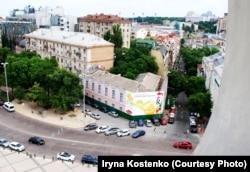 Вигляд на «будинок з балконом Грушевського» (закритий будівельним банером) із дзвіниці Софії Київської. Київ, червень 2018 року