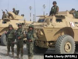 سربازان افغان در کنار تجهیزات آمریکایی هدیه شده به ارتش آمریکا در قندهار در فوریه ۲۰۱۵