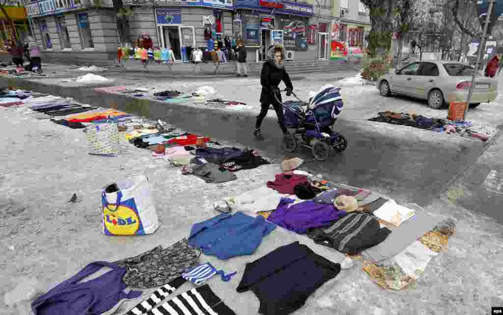 A Moldovan woman pushes a baby stroller while passing a flea market were people sell secondhand goods, displayed on the pavement, on a boulevard in Chisinau, Moldova. (epa/Robert Ghement)