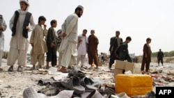 FILE: Afghan men walk amidst sandals, mostly from victims of a bomb blast, strewn at the roadside on the outskirts of Kandahar city in August 2013.