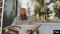 Iran, Tehran -- A man reads a newspaper