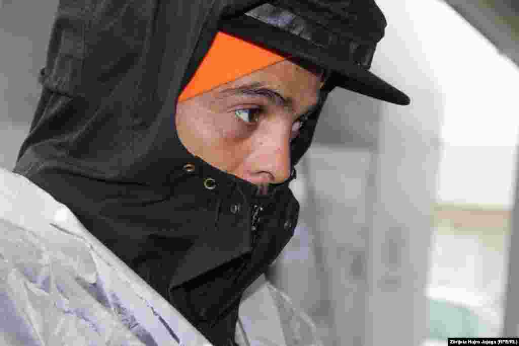 Një migrant pret të ndalet shiu për të vazhduar rrugën ilegalisht drejt Serbisë, përmes shtigjeve malore.