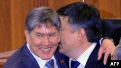 Newly elected prime minister of Kyrgyzstan, Almazbek Atambaev (L), is congratulated by the newly elected parliament speaker Akhmatbek Keldibekov.