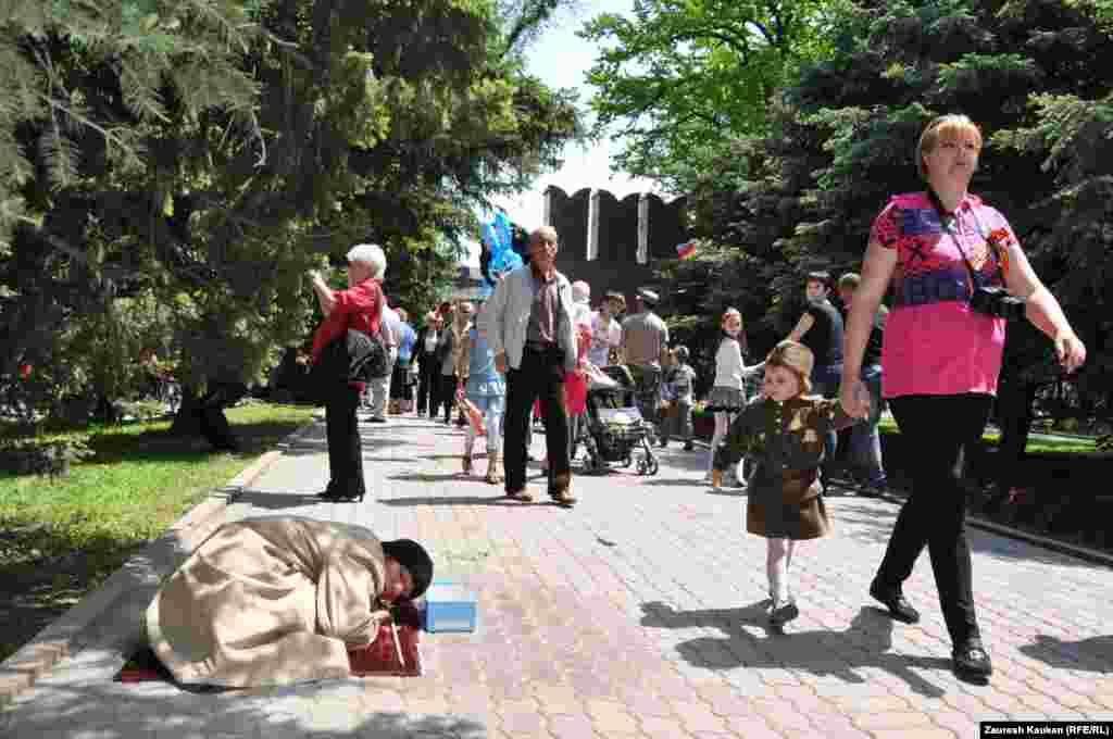 Женщина собирает милостыню на праздновании Дня Победы в Парке имени 28 гвардейцев-панфиловцев. Алматы, 9 мая 2013 года.