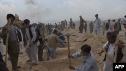 Men dig graves for victims of the July 23 attack in Kabul.