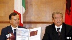 Albania -- Italian Foreign Minister Franco Frattini (L) checks the new Albanian biometric passport and ID card presented to him by Albanian Prime Minister Sali Berisha at a press conference in Tirana, 27Oct2008