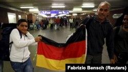 Migrantët e mbajnë flamurin gjerman me të arritur në këtë vend