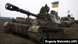Ukrainian servicemen ride atop armored vehicles on the outskirts of Donetsk.