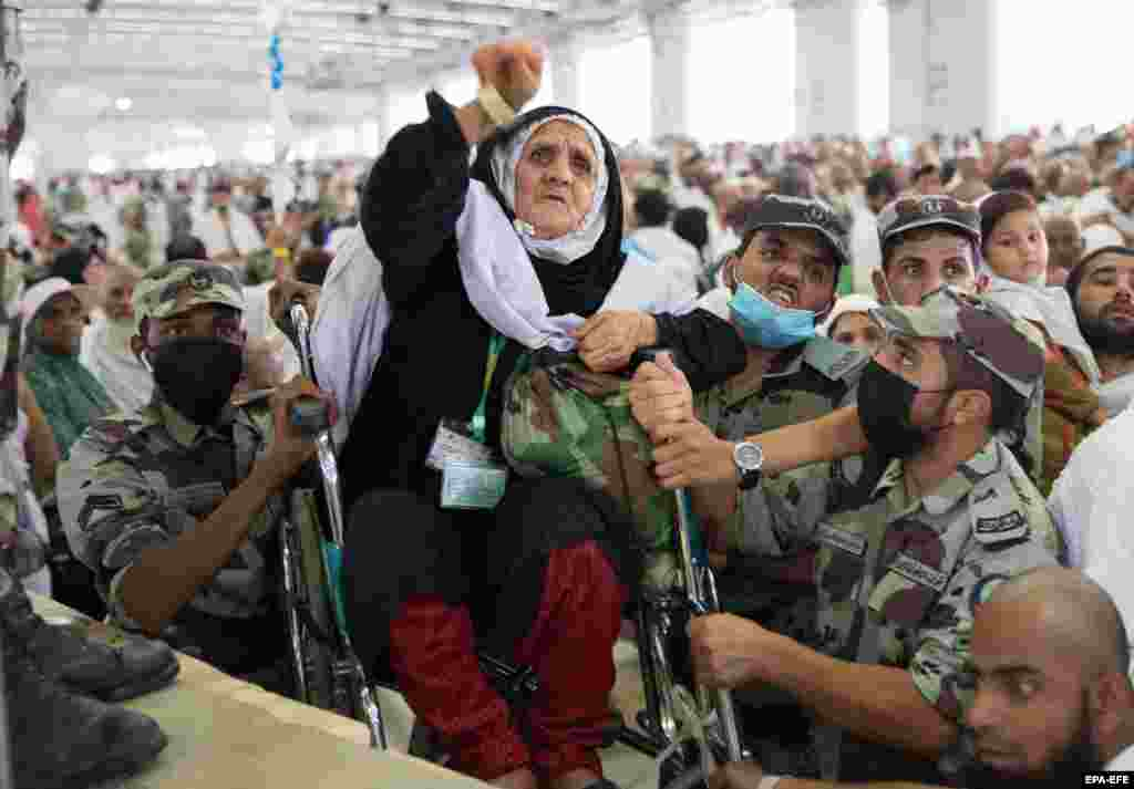 Saudi soldiers carry a woman in a wheelchair as she throws pebbles as part on the symbolic stoning of the devil ritual at the Jamarat Bridge during the hajj pilgrimage near Mecca on August 11. (epa-EFE)