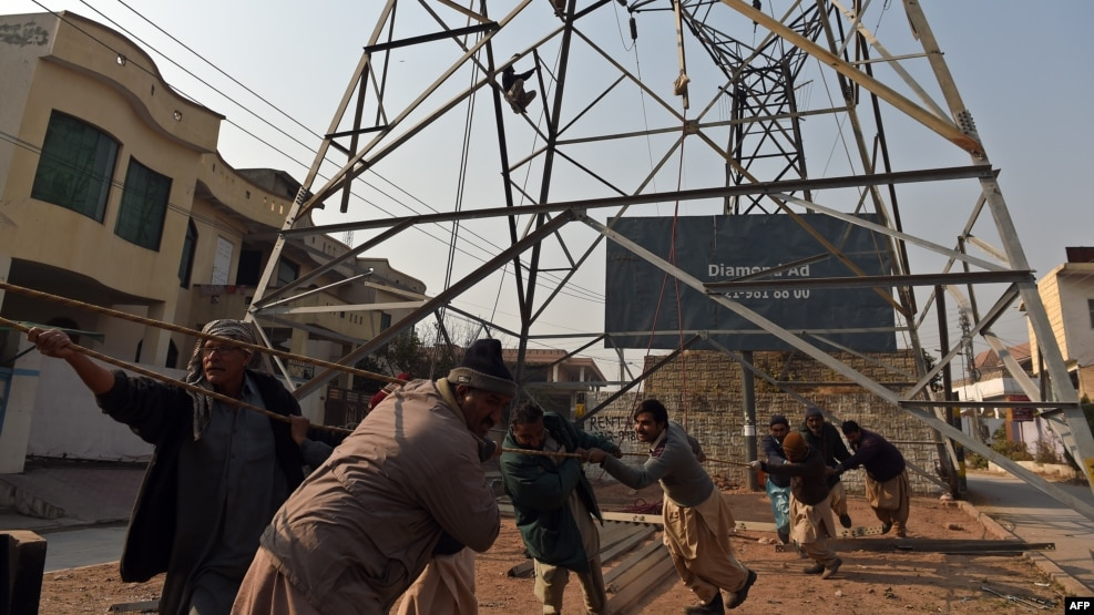 Pakistani workers complete a high-voltage power pole in Rawalpindi. (file photo)