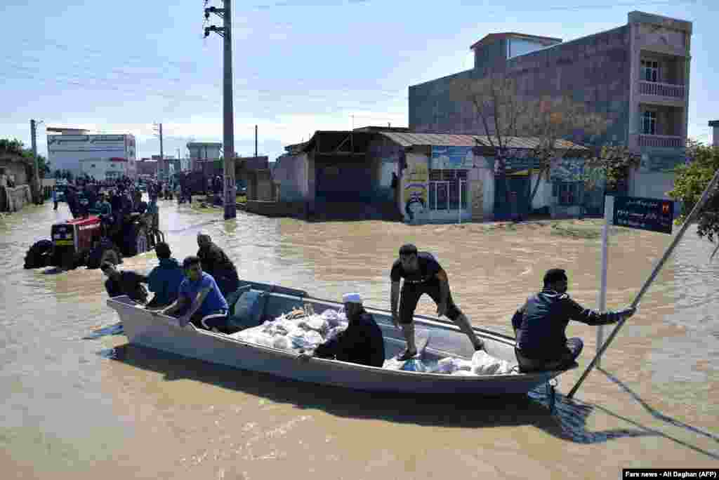 Residents of the northern Iranian village Agh Ghaleh are using a boat in a flooded street, on March 23, 2019.