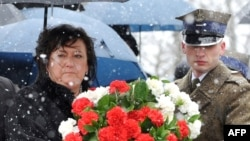 Polish first lady Anna Komorowska prepares to lay flowers at the monument for the 96 victims of the April 2010 plane crash during a memorial service at the Smolensk aerodrome, the site of the disaster.