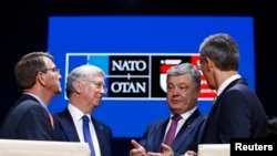 U.S. Defense Secretary Ash Carter, British Defense Secretary Michael Fallon, Ukrainian President Petro Poroshenko, and NATO Secretary-General Jens Stoltenberg in Warsaw