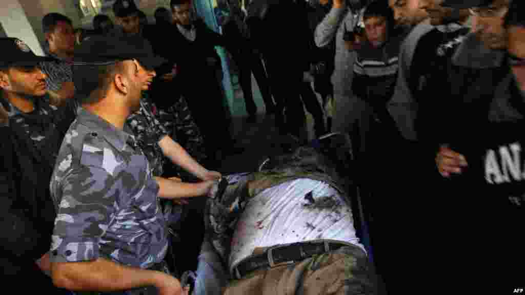 Security forces wheel the body of Ahmed al-Jaabari into a hospital.
