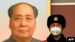 Китайский полицейский на площади Тяньаньмэнь в Пекине напротив портрета Мао Цзэдуна. Февраль 2002 года.