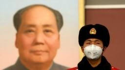 Китайский полицейский на площади Тяньаньмэнь в Пекине на фоне портрета Мао Цзэдуна. Февраль 2002 года