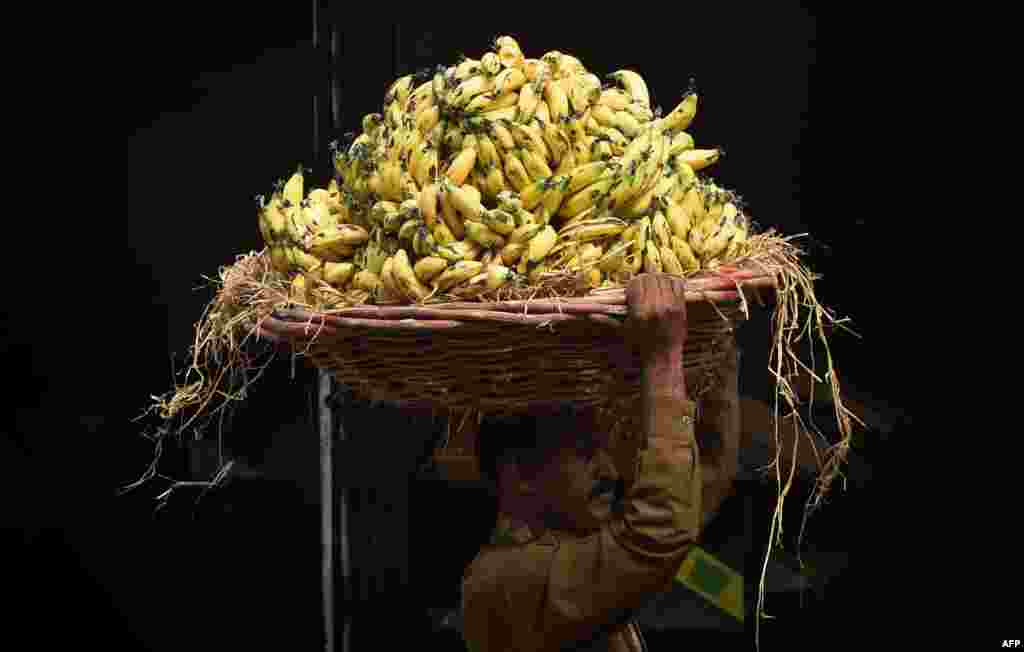 A Pakistani laborer carries a basket of bananas at a fruit market in Lahore. (AFP/Arif Ali)