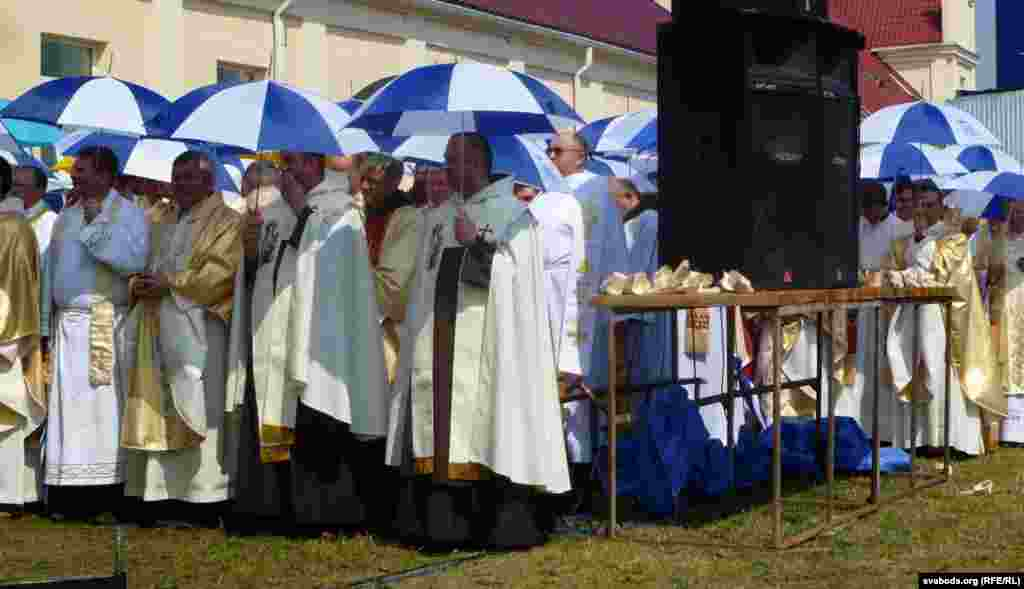 Clergy shelter under umbrellas during a pilgrimage in Budslau, Belarus, which houses the National Sanctuary of the Mother of God of Budslau.