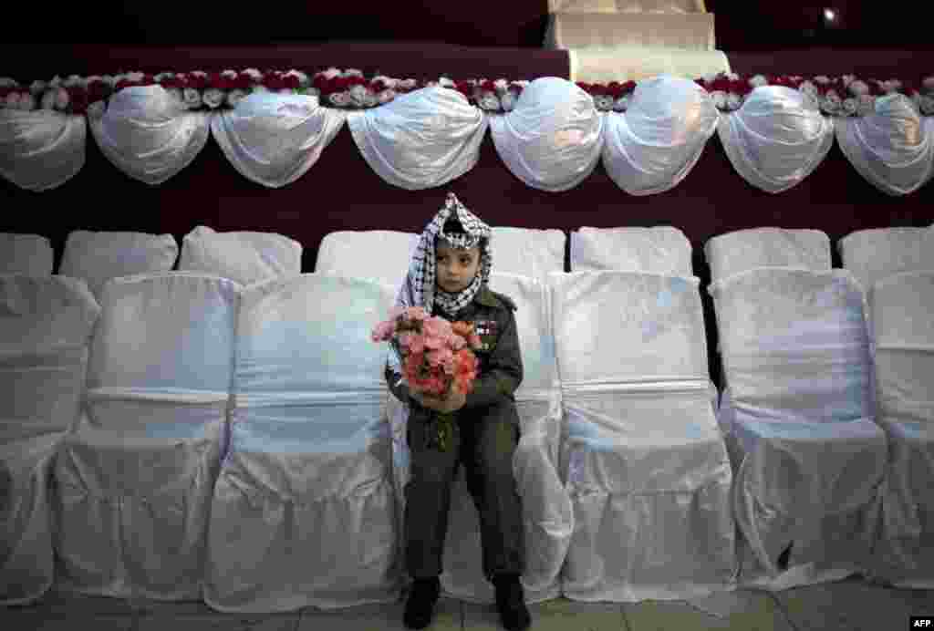 A young Palestinian wearing a traditional Keffiyeh head scarf carries a bouquet of flowers ahead of a mass wedding ceremony in Gaza City. (AFPMahmud Hams)