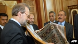 Iranian Parliament Speaker Ali Larijani (L) offers Yemeni President Ali Abdullah Saleh (R) a Persian carpet during their meeting in Sanaa on May 14, 2009. Larijani is on an official visit to neighbouring Yemen. AFP PHOTO/KHALED FAZAA / AFP PHOTO / KHALED
