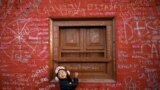 A Nepalese girl looks toward her father as she writes on the wall of a Saraswati temple during the Shreepanchami festival in Kathmandu on February 11. (Reuters/Navesh Chitrakar)