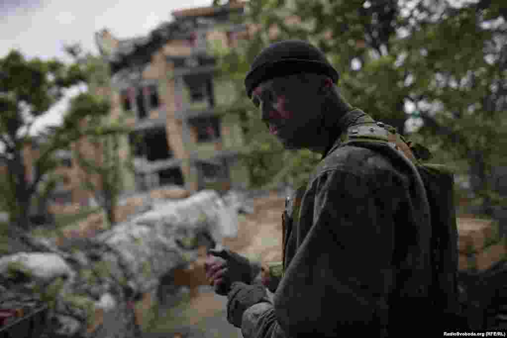 Serhiy, a group commander, stands by the ruins of a former sanatorium destroyed in the fighting. The soldiers use the shell of the building for shelter.