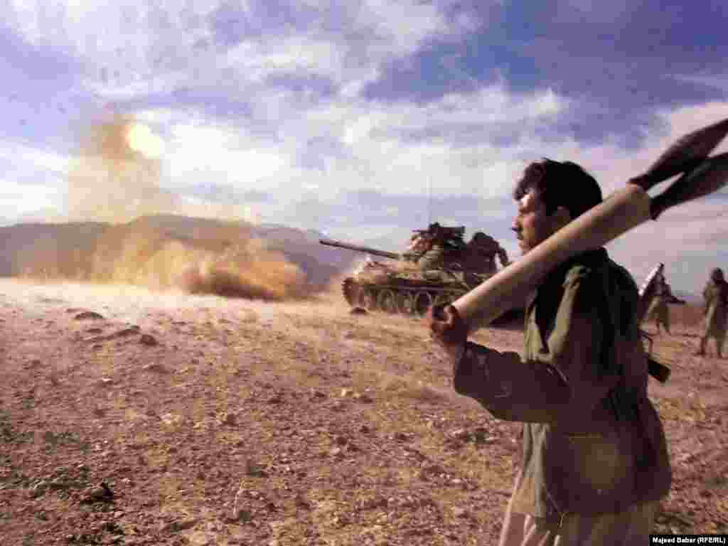 """Afghan fighters shelling Al-Qaeda positions in Tora Bora where Osama bin Laden was reportedly hiding in December 2001. Афганскія ваяўнікі абстрэльваюць пазыцыі """"Аль-Каіды"""", дзе, паводле некаторых паведамленьняў хаваўся бін Лядэн, сьнежань 2001"""