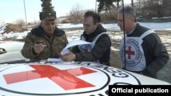 Armenia - An Armenian military official and representatives of the Red Cross prepare for the handover to Azerbaijan of the body of an Azerbaijani army soldier killed on the Armenian-Azerbaijani border on December 29, 5Feb2017.
