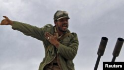 A rebel fighter reacts to incoming shells fired by soldiers loyal to Moammar Qaddafi. The rebels started out strong, but appear to be losing territory day-by-day.