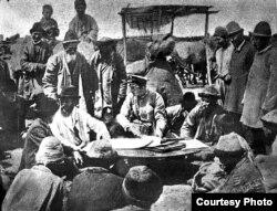 Кыргыздарды келгиндерге берилчү жерлердин планы менен тааныштырууда.