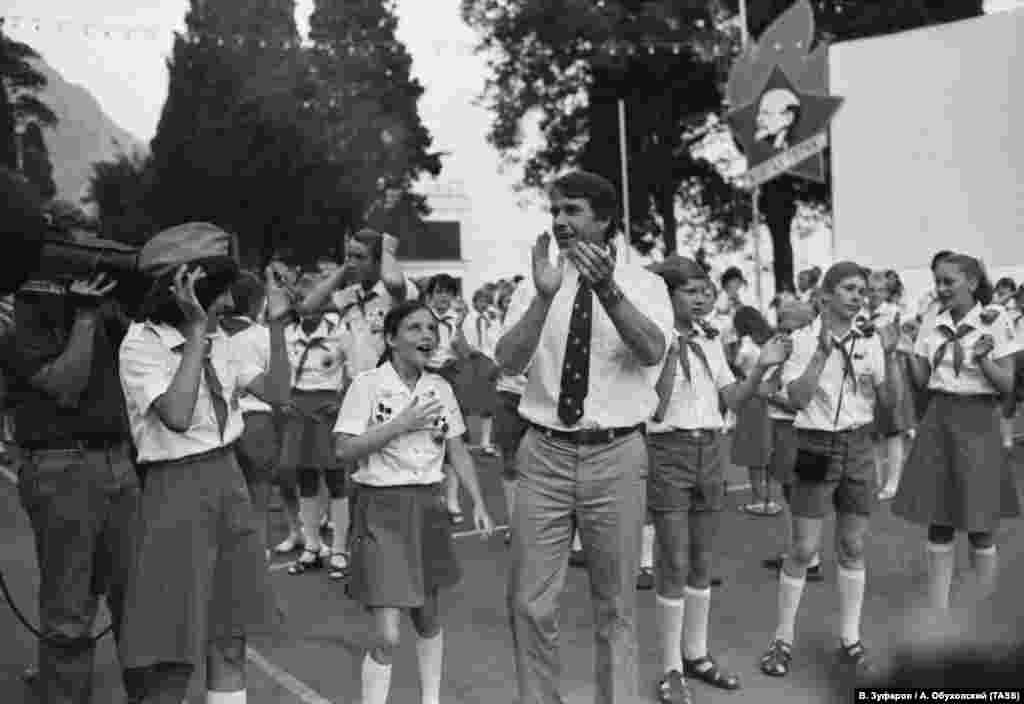 Последний день Саманы Смит в «Артеке» припал на окончание очередной смены. Шествия, танцы, маскарад и фейерверки – девочка вспоминала это словами «грандиозное зрелище» и удивлялась тому, что праздник заставил танцевать даже ее родителей. На фото: Саманта с отцом, Артуром Смитом, в окружении детей и журналистов