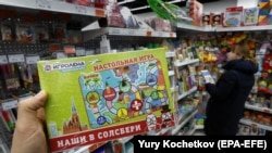 A customer holds an Our Guys In Salisbury board game in a shop in Moscow.