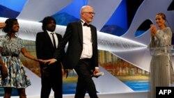 Француз режиссері Жак Одиар (ортада) Канн кинофестивалінің басты жүлдесін алу кезінде. Франция, 24 мамыр 2015 жыл.