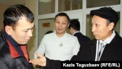 Юрист Сакен Шардаров (справа) говорит с Сериком Ембергеновым (слева), бывшим одноклассником Екпина (в центре), в здании суда. Алматы, 4 января 2012 года.