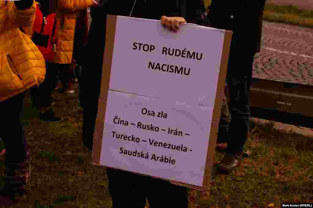 Плакат в руках одного из пришедших на церемонию: «Остановить красный нацизм. Ось зла: Китай – Россия– Иран– Турция– Венесуэла– Саудовская Аравия».