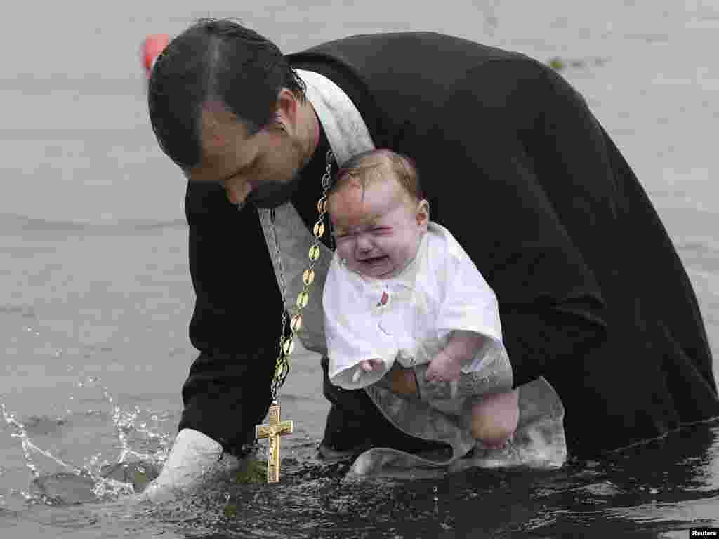 An Orthodox priest baptizes a child in a river during a ceremony marking the adoption of Christianity, outside the Russian city of Nazarovo, some 200 kilometers west of Krasnoyarsk. On July 28, Russia officially celebrated a new holiday marking its conversion to Christianity in 988. Photo by Ilya Naymushin for Reuters