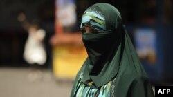 A Uyghur woman walks on a street in Urumqi, the capital of China's Xinjiang region. (file photo)