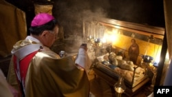 Bethlehem - Latin Patriarch of Jerusalem Fouad Twal blesses a statue of the baby Jesus inside in the Grotto where Christians believe the Virgin Mary gave birth to Jesus following a Christmas Midnight Mass in the Church of the Nativity in the West Bank tow