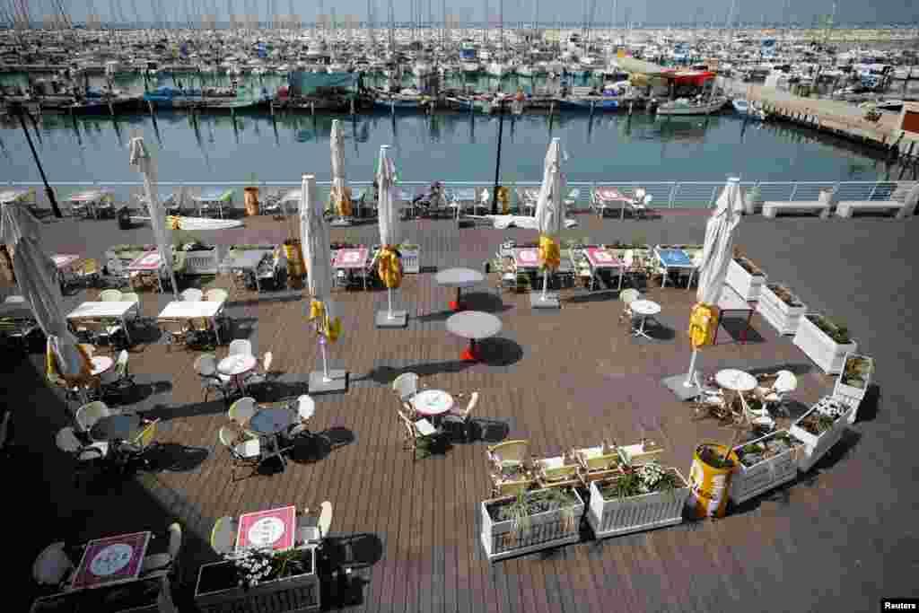 Оставшийся без гостей ресторан на пристани в Ашкелоне на юге Израиля. 15 марта 2020 года. Правительство Биньямина Нетаньяху объявило о закрытии с 15 марта торговых центров, отелей, ресторанов и театров. В Израиле менее двух тысяч подтвержденных случаев COVID-19.